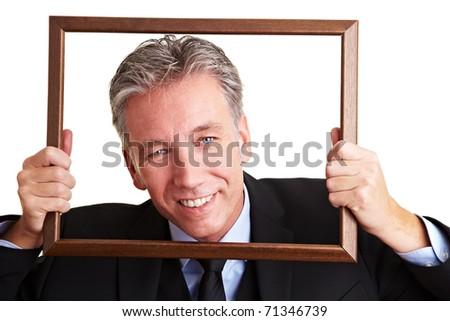 Smiling senior business man looking through an empty frame - stock photo