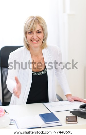 Smiling senior business woman stretching hand for handshake