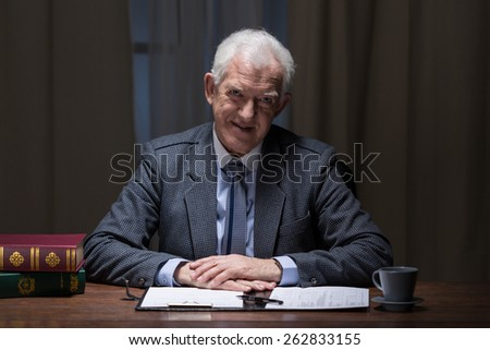 Smiling senior businessman at the workplace - stock photo