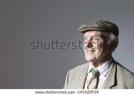 Smiling senior businessman in flat cap against gray background - stock photo