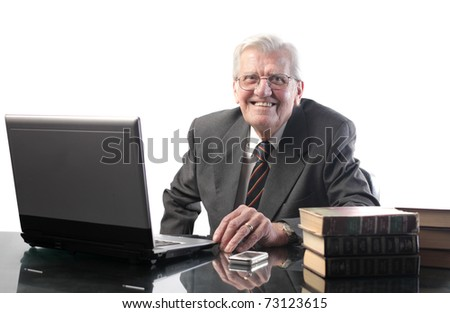Smiling senior businessman in front of a laptop - stock photo