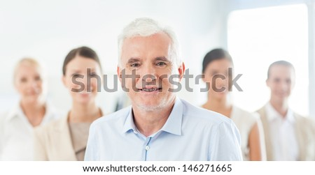 Smiling senior businessman in front of his business team. - stock photo