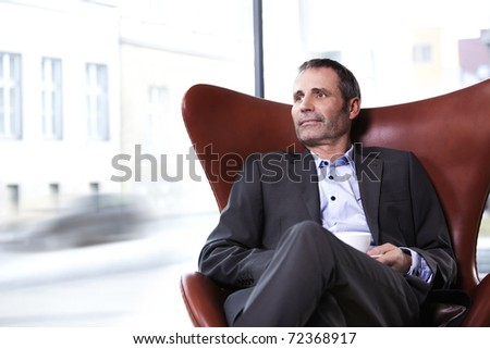 Smiling senior businessman in grey suit sitting in office in red chair looking outside and enjoying a cup of coffee. - stock photo
