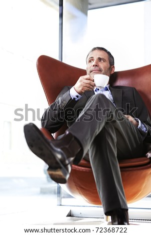 Smiling senior businessman in grey suit sitting in red office chair looking outside and enjoying a cup of coffee with bright background.