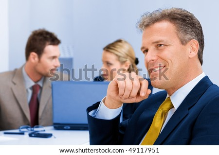 Smiling senior businessman looking away with positive expression at the bright future of the company - stock photo