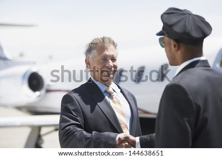 Smiling senior businessman shaking hands with pilot and blurred aircraft in the background - stock photo