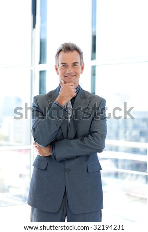 Smiling senior businessman standing in office - stock photo