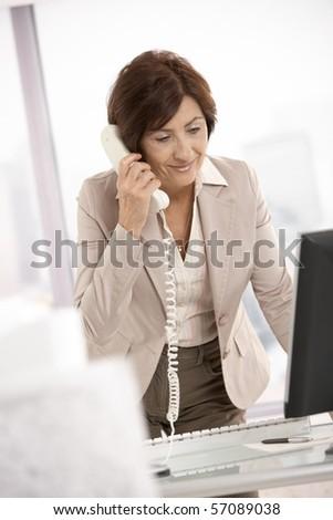 Smiling senior businesswoman talking on landline phone at desk, smiling.? - stock photo