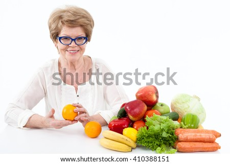 Smiling senior Caucasian woman holding hands two oranges, vegetables and fruits are on table, white background - stock photo
