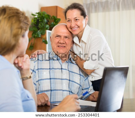 Smiling senior couple answer questions of social worker at home. Focus on man  - stock photo