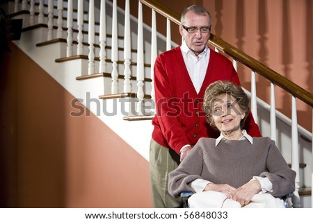Smiling senior couple at home, woman in wheelchair
