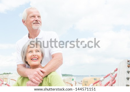 Smiling senior couple at the beach - stock photo
