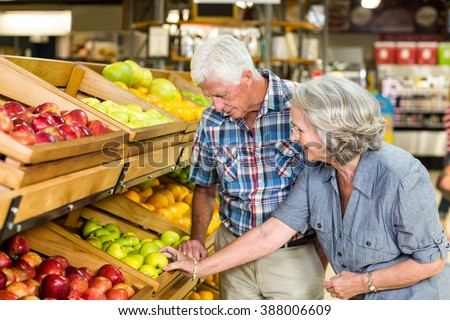 Smiling senior couple buying apples at the grocery shop - stock photo