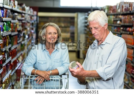 Smiling senior couple buying food at the supermarket - stock photo