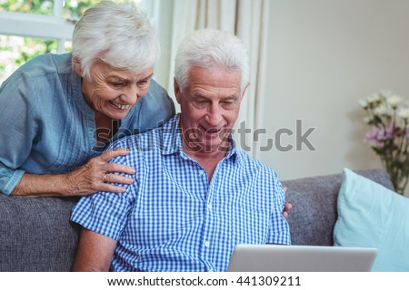 Smiling senior couple discussing while using laptop at home - stock photo