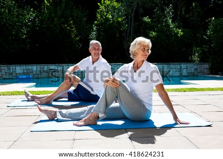 Smiling senior couple exercising on mat at poolside