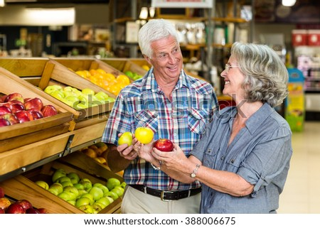 Smiling senior couple holding apples at the grocery shop - stock photo
