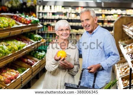 Smiling senior couple holding fruit at the grocery shop - stock photo