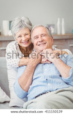 Smiling senior couple hugging while sitting on sofa at home - stock photo