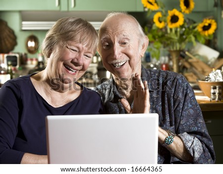 Smiling Senior Couple in their Dining Room with a Laptop Computer - stock photo