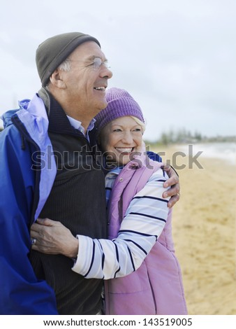Smiling senior couple in winter clothing embracing at beach - stock photo