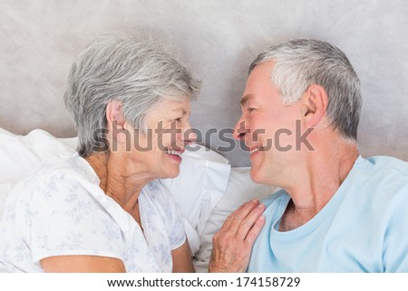 Smiling senior couple looking at each other in bed - stock photo