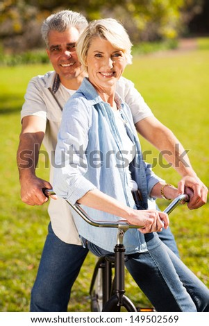 smiling senior couple on a bicycle outdoors - stock photo