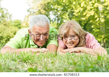 Smiling senior couple relaxed on green grass..