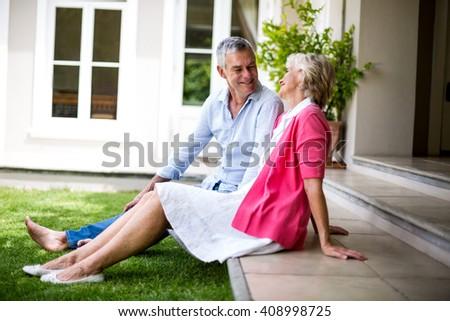 Smiling senior couple sitting on steps outside house at yard - stock photo