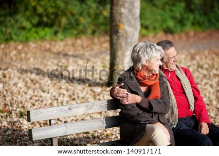 Smiling senior couple sitting on the bench park while looking at something - stock photo
