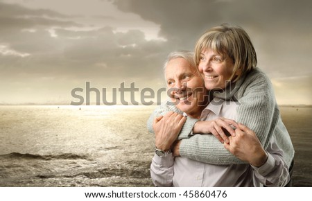 Smiling senior couple standing at the seaside at sunset - stock photo