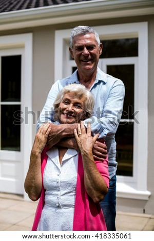 Smiling senior couple standing with arms around outside house at yard - stock photo