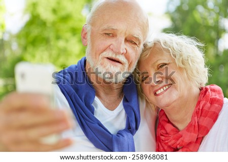 Smiling senior couple taking selfie portrait with smartphone in nature - stock photo