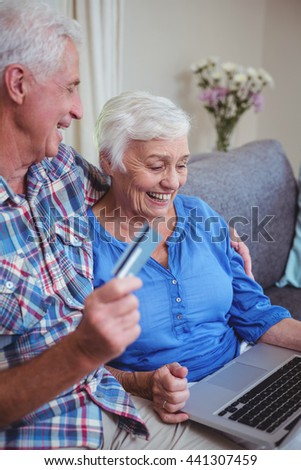 Smiling senior couple using credit card and laptop at home - stock photo
