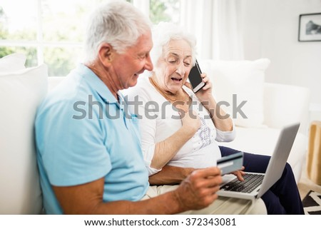 Smiling senior couple using laptop and smartphone at home - stock photo