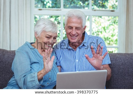 Smiling senior couple waving hand while using laptop at home - stock photo