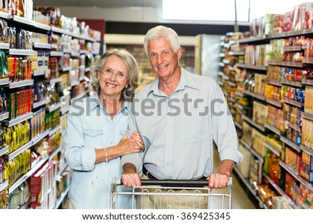 Smiling senior couple with cart at the supermarket