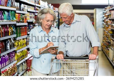 Smiling senior couple with cart checking list at the supermarket