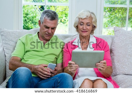 Smiling senior couple with digital tablet and mobile phone at home