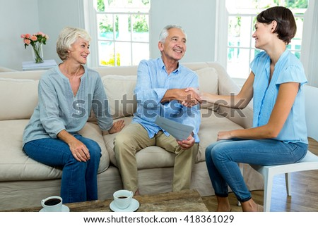 Smiling senior couple with female consultant sitting on sofa at home - stock photo