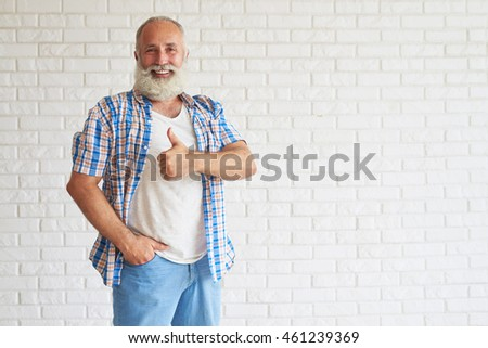 Smiling senior dressed in jeans with checkered shirt standing and holding thumbs up, white brick wall in background