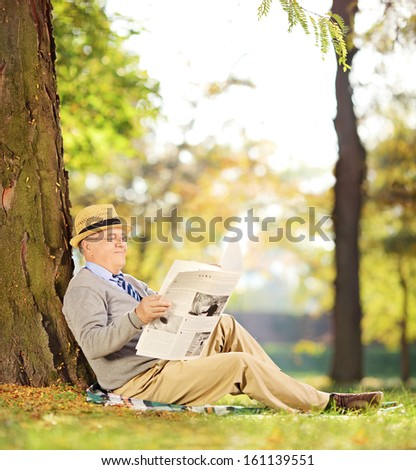 Smiling senior gentleman seated on a grass reading a newspaper in a park at autumn, shot with a tilt and shift lens - stock photo