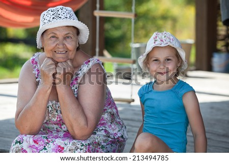 Smiling senior grandmother and happy grandchild sitting on summer veranda  - stock photo