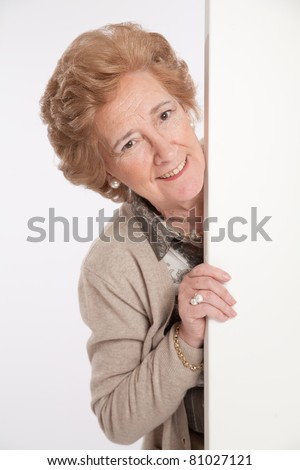 Smiling senior lady holding a blank board