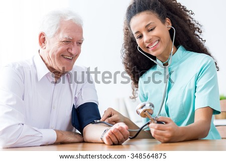 Smiling senior man having measured blood pressure - stock photo