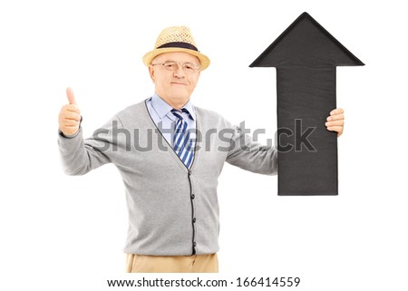 Smiling senior man holding a black arrow pointing up and giving a thumb up isolated on white background - stock photo