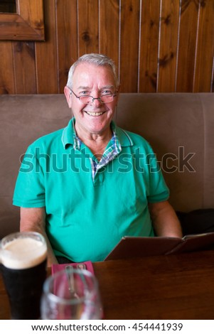 Smiling senior man holding a restaurant menu and having a pint of Stout beer - stock photo