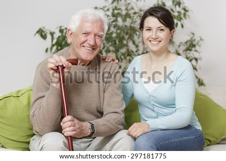 Smiling senior man holding can and supporting granddaughter - stock photo