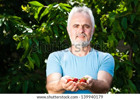 smiling senior man holding strawberry