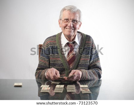 Smiling senior man playing cards - stock photo